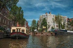 De grote die boot als huis wordt gebruikt legde aan kant van tree-lined kanaal met oude gebouwen en zonnige blauwe hemel in Amste Royalty-vrije Stock Foto
