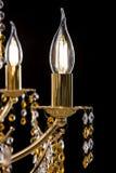 De grote die kroonluchter van het kristalclose-up met kaarsen op zwarte achtergrond worden geïsoleerd Stock Foto's