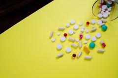 De grote en heldere rode en witte, kleurrijke pillen zijn verspreid die van een glas op een gele achtergrond wordt geïsoleerd Med royalty-vrije stock fotografie