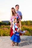 De grote familie in etnische Oekraïense kostuums zit op de weide, het concept een grote familie stock foto
