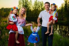 De grote familie in etnische Oekraïense kostuums zit op de weide, het concept een grote familie stock fotografie