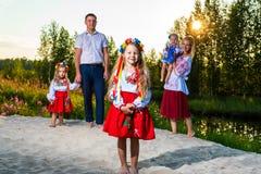 De grote familie in etnische Oekraïense kostuums zit op de weide, het concept een grote familie stock afbeeldingen