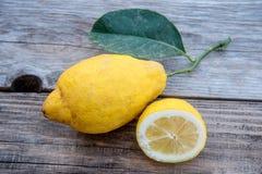 De grote gele citroen ligt op een blauwe plaat op een gele achtergrond Royalty-vrije Stock Afbeelding