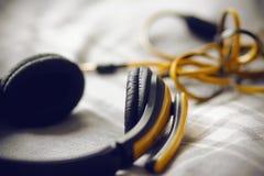 De grote gele hoofdtelefoons liggen op een grijze plaid stock fotografie