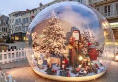 De grote glasbal die met de Kerstman in een straat bevatten verfraaide voor Kerstmis Royalty-vrije Stock Foto
