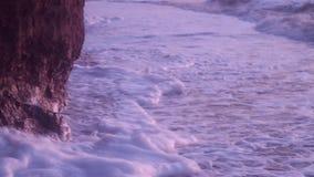 De grote golven, met overzees schuim van witte kleur, slaan tegen het strand met nat zand, kleirots, tegen een blauwe hemel stock videobeelden