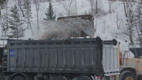 De grote graafwerktuig` s emmer laadt rotsen aan kipwagenvrachtwagen in een steengroeve bovengrondse mijnbouw, de geologie Uren e stock video