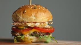 De grote Hamburger met rundvleeskotelet, tomaten, paddestoelen en komkommers met gesmolten kaas roteert op een houten Raad op lic stock videobeelden