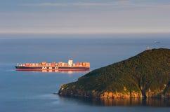 De grote het bedrijfdoctorandus in de exacte wetenschappen wordt van het containerschip verankerd in de baai bij zonsondergang De Royalty-vrije Stock Afbeelding