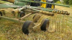 De grote het oogsten machine draait boven droog gras, vrachtwagen met hooimaker die aan de weide in landbouwgrond werken stock video