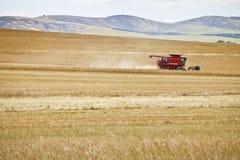 De grote het oogsten machinewerken door gebied royalty-vrije stock foto's