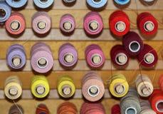 De grote hoeveelheid spoelen met kleurrijke draden voor het naaien Stock Fotografie