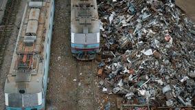 De grote hopen van metaalschroot en containers met huisvuil zijn dichtbij een spoorweg met treinen in dag in bewolkt weer, stock video