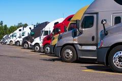 De grote installaties semi vrachtwagens van verschillend maakt en modelleert tribune in rij stock afbeeldingen