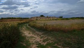 De grote keien in Barrens liggen op het zand amid de donkerblauwe hemel vóór de de zomerregen royalty-vrije stock afbeelding