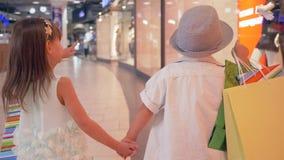 De grote kortingen, Modieuze kinderen gaan voorbij winkelvensters met modellen na aankopen op dure boutiques in wandelgalerij stock videobeelden