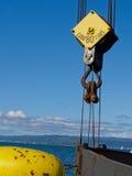 De grote kraankatrol hangt boven boog van baggermachineboot. Stock Afbeeldingen