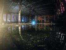 De grote lege verlaten pakhuisbouw of de fabrieksworkshop bij nacht met bezinning in water, samenvatting ruïneren achtergrond royalty-vrije stock afbeelding