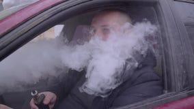 De grote mens rookt vape in de auto en produceert rook stock footage