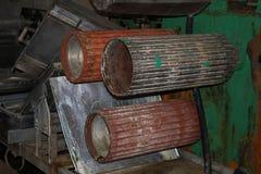 De grote metaalrollen rolt met tanden van de toestellen van de productielijn, een transportband in de workshop bij een industriee royalty-vrije stock foto