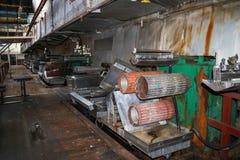 De grote metaalrollen rolt met tanden van de toestellen van de productielijn, een transportband in de workshop bij een industriee royalty-vrije stock fotografie