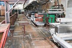 De grote metaalrollen rolt met tanden van de toestellen van de productielijn, een transportband in de workshop bij een industriee stock afbeeldingen