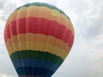 De grote multi-colored heldere ronde regenboog kleurde gestreepte gestreepte vliegende ballon met een mand tegen de hemel in de a stock afbeelding