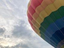 De grote multi-colored heldere ronde regenboog kleurde gestreepte gestreepte vliegende ballon met een mand tegen de hemel in de a royalty-vrije stock afbeeldingen