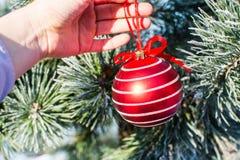De grote rode bal die van Kerstmisdecoratie in hand openlucht houden Stock Foto