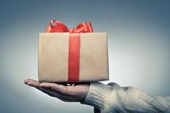 De grote rode doos van de lintgift op een hand Het concept van giftdozen voor GIF Stock Foto's