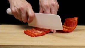 De grote rode groene paprika's zijn gescheiden en de kern wordt verwijderd De chef-kok houdt een mes in vrouwelijke handen en sni stock videobeelden