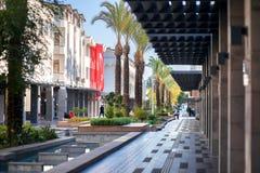De grote rode Turkse vlag hangt op één van huizen De voet Turkse straat met de fontein in de stad van Kemer stock fotografie