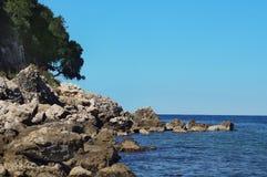 De grote rotsen en de rotsen op het strand, bomen groeien op de richels Royalty-vrije Stock Foto