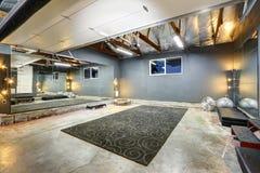 De grote ruimte van de kelderverdiepingsgymnastiek met spiegel Stock Afbeeldingen