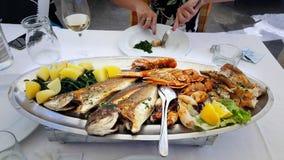 De grote schotel met de heerlijke oesters en de kammosselen op ijs met vissen, geroosterde kalk, diende met champagne en fijne kr Royalty-vrije Stock Afbeeldingen