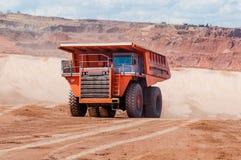 De grote stortplaatsvrachtwagen ontgint machines, of mijnbouwmateriaal aan trans stock foto