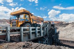 De grote stortplaatsvrachtwagen ontgint machines, of mijnbouwmateriaal aan trans royalty-vrije stock fotografie