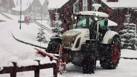 De grote tractor maakt sneeuw op de straat schoon stock video