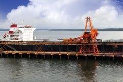 De grote transportband laadt ladingen van steenkool aan schip Royalty-vrije Stock Foto