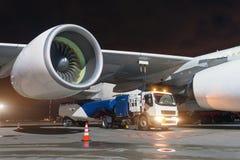 De grote vliegtuigenstraalmotoren, die een reusachtig vliegtuig van brandstof voorzien, een vrachtwagen met brandstof met slangen royalty-vrije stock afbeelding