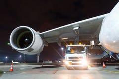 De grote vliegtuigenstraalmotoren, die een reusachtig vliegtuig van brandstof voorzien, een vrachtwagen met brandstof met slangen stock afbeelding