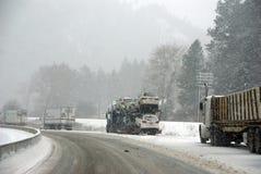 De grote vrachtwagens bestrijden een de winteronweer Stock Foto