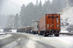 De grote vrachtwagens bestrijden een de winteronweer Stock Foto's