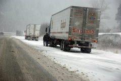 De grote vrachtwagens bestrijden een de winteronweer Stock Afbeeldingen