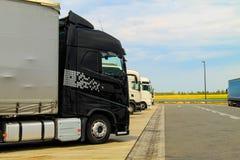 De grote vrachtwagens van zwart-wit worden geparkeerd dichtbij de weg Het leveren of Leveringsconcept Wegtrein royalty-vrije stock foto