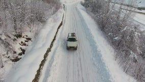De grote witte auto berijdt op sneeuw behandelde weg onder berijpte bomen op de winterdag stock video
