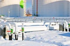 De grote witte industriële tanks van het ijzermetaal voor opslag van brandstof, benzine en diesel en pijpleiding met kleppen en f stock afbeeldingen