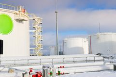 De grote witte industriële tanks van het ijzermetaal voor opslag van brandstof, benzine en diesel en pijpleiding met kleppen en f royalty-vrije stock afbeelding