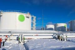 De grote witte industriële tanks van het ijzermetaal voor opslag van brandstof, benzine en diesel en pijpleiding met kleppen en f royalty-vrije stock fotografie
