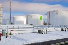 De grote witte industriële tanks van het ijzermetaal voor opslag van brandstof, benzine en diesel en pijpleiding met kleppen en f stock afbeelding